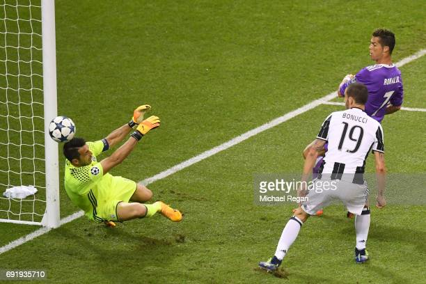 Cristiano Ronaldo of Real Madrid scores his sides third goal past Gianluigi Buffon of Juventus during the UEFA Champions League Final between...