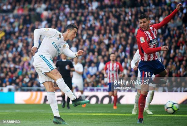 Cristiano Ronaldo of Real Madrid scores his team's first goal past Lucas Hernandez of Atletico de Madrid during the La Liga match between Real Madrid...
