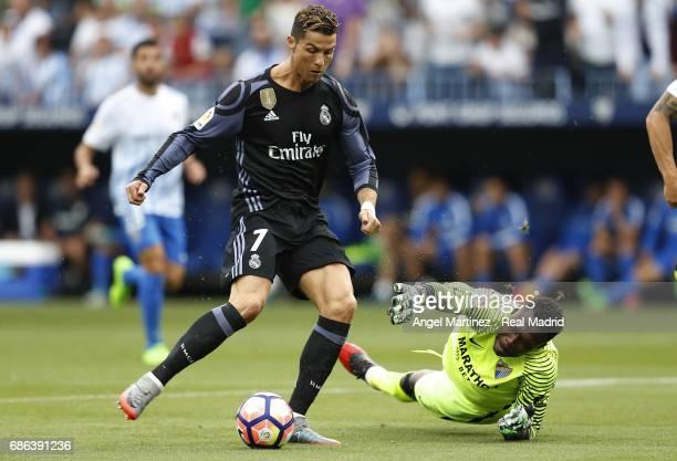 Cristiano Ronaldo of Real Madrid scores the opening goal past Carlos Kameni of Malaga CF during the La Liga match between Malaga CF and Real Madrid...