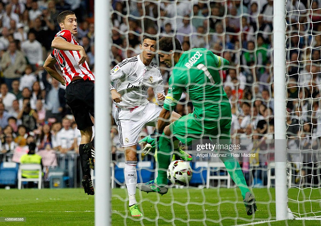 Cristiano Ronaldo of Real Madrid scores the opening goal past Oscar de Marcos (L) and Gorka Iraizoz of Athletic Club during the La Liga match between Real Madrid CF and Athletic Club at Estadio Santiago Bernabeu on October 5, 2014 in Madrid, Spain.