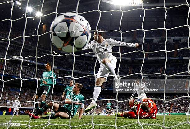 Cristiano Ronaldo of Real Madrid scores the opening goal past goalkeeper Ralf Fahrmann of FC Schalke 04 during the UEFA Champions League Round of 16...
