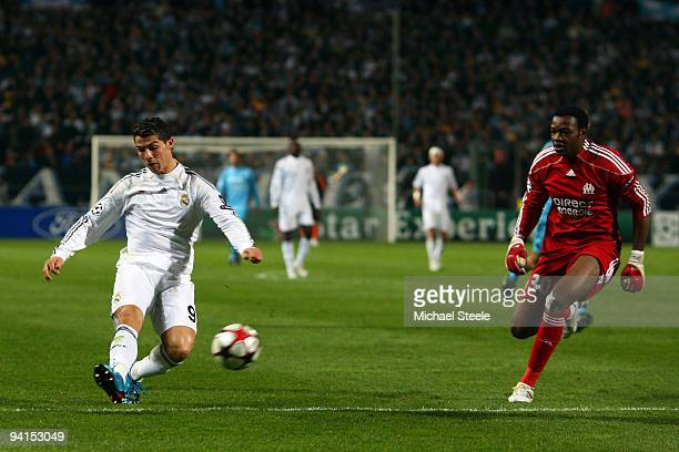 Cristiano Ronaldo of Real Madrid scores the third goal as goalkeeper Steve Mandanda of Marseille looks on during the Marseille and Real Madrid UEFA...
