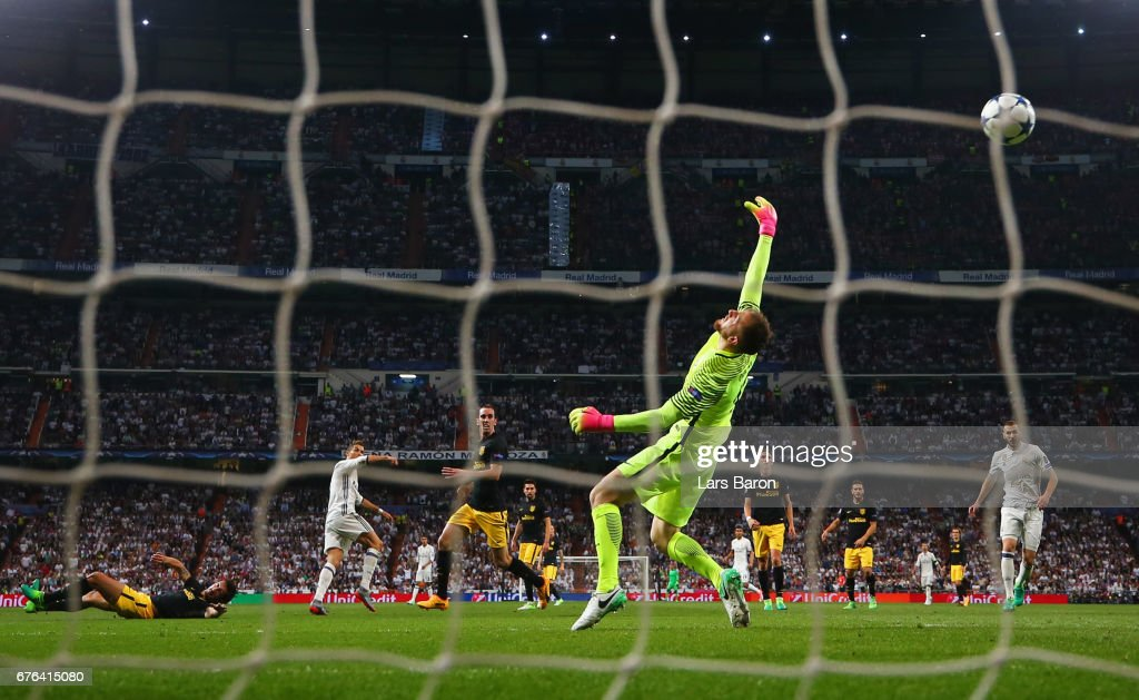 Cristiano Ronaldo of Real Madrid (2L) scores their second goal past goalkeeper Jan Oblak of Atletico Madrid during the UEFA Champions League semi final first leg match between Real Madrid CF and Club Atletico de Madrid at Estadio Santiago Bernabeu on May 2, 2017 in Madrid, Spain.