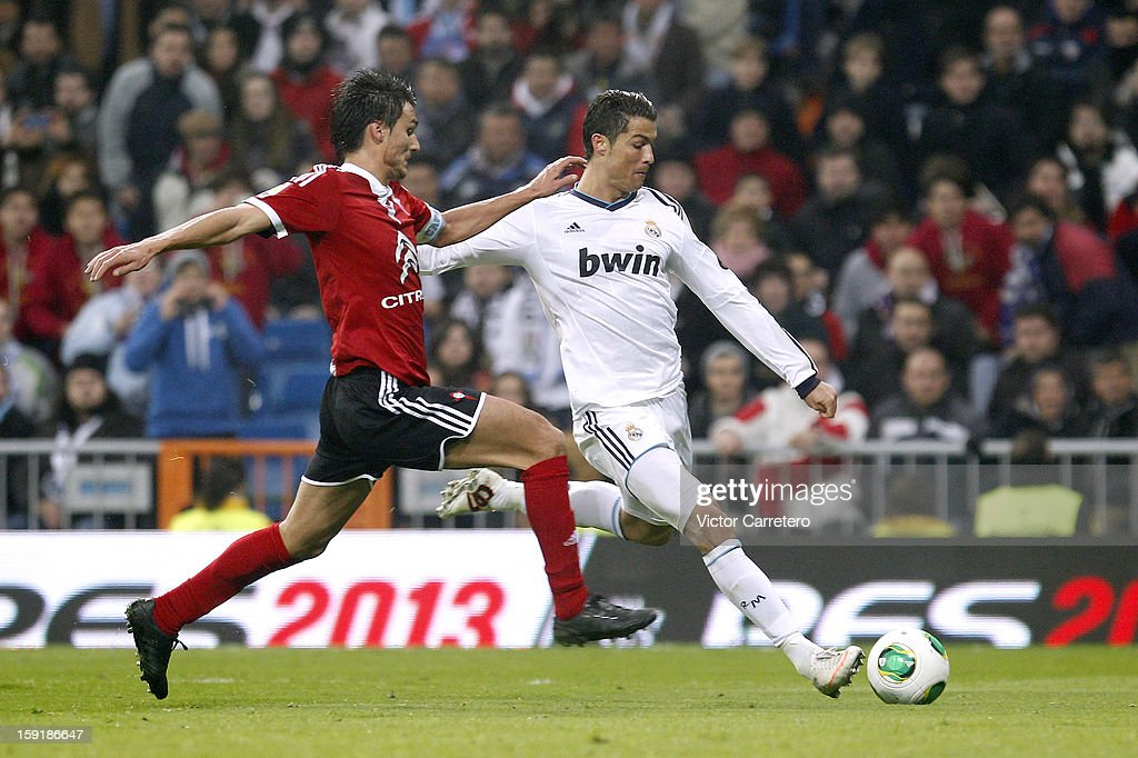 Cristiano Ronaldo (R) of Real Madrid scores their third goal past Carlos Bellvis of Celta de Vigo during the Copa del Rey round of 16 second leg match between Real Madrid and Celta de Vigo at Estadio Santiago Bernabeu on January 9, 2013 in Madrid, Spain.