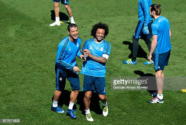 Cristiano Ronaldo of Real Madrid shares a joke with Marcelo of Real Madrid during a training session ahead of the UEFA Champions League Semi Final...