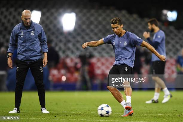 Cristiano Ronaldo of Real Madrid shoots as Zinedine Zidane Manager of Real Madrid looks on during a Real Madrid training session prior to the UEFA...