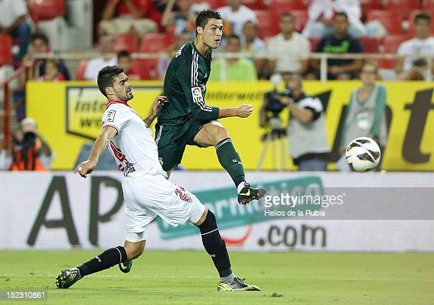 Cristiano Ronaldo of Real Madrid shoots on goal under pressure from Alberto Botia of Sevilla during the La Liga match between Sevilla FC and Real...