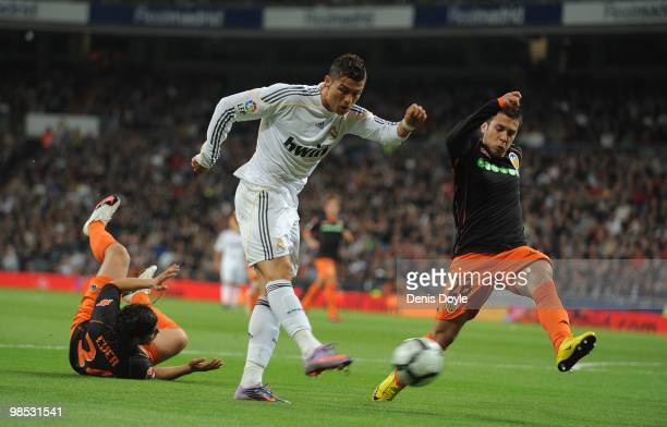Cristiano Ronaldo of Real Madrid shoots past Ever Banega and Jordi Alba of Valencia during the La Liga match between Real Madrid and Valencia at...