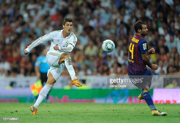 Cristiano Ronaldo of Real Madrid shoots past Javer Mascherano of Barcelona during the Super Cup first leg match between Real Madrid and Barcelona at...