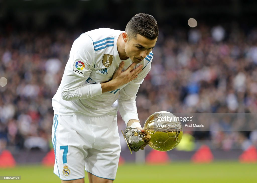 Cristiano Ronaldo of Real Madrid shows his recent won Golden Ball (Ballon d'Or) trophy prior to start the La Liga match between Real Madrid and Sevilla at Estadio Santiago Bernabeu on December 9, 2017 in Madrid, Spain.