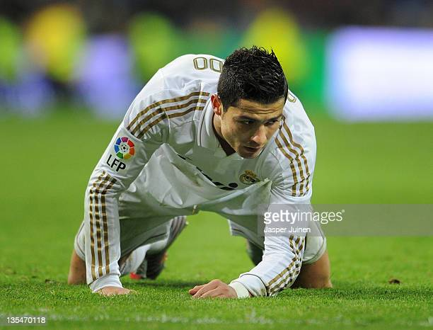 Cristiano Ronaldo of Real Madrid sits on his knees as he reacts after failing to score during the la Liga match between Real Madrid and Barcelona at...