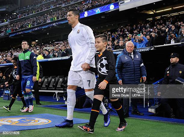 Cristiano Ronaldo of Real Madrid takes to the field with a player escort in the UEFA Champions League Quarter Final Second Leg match between Real...