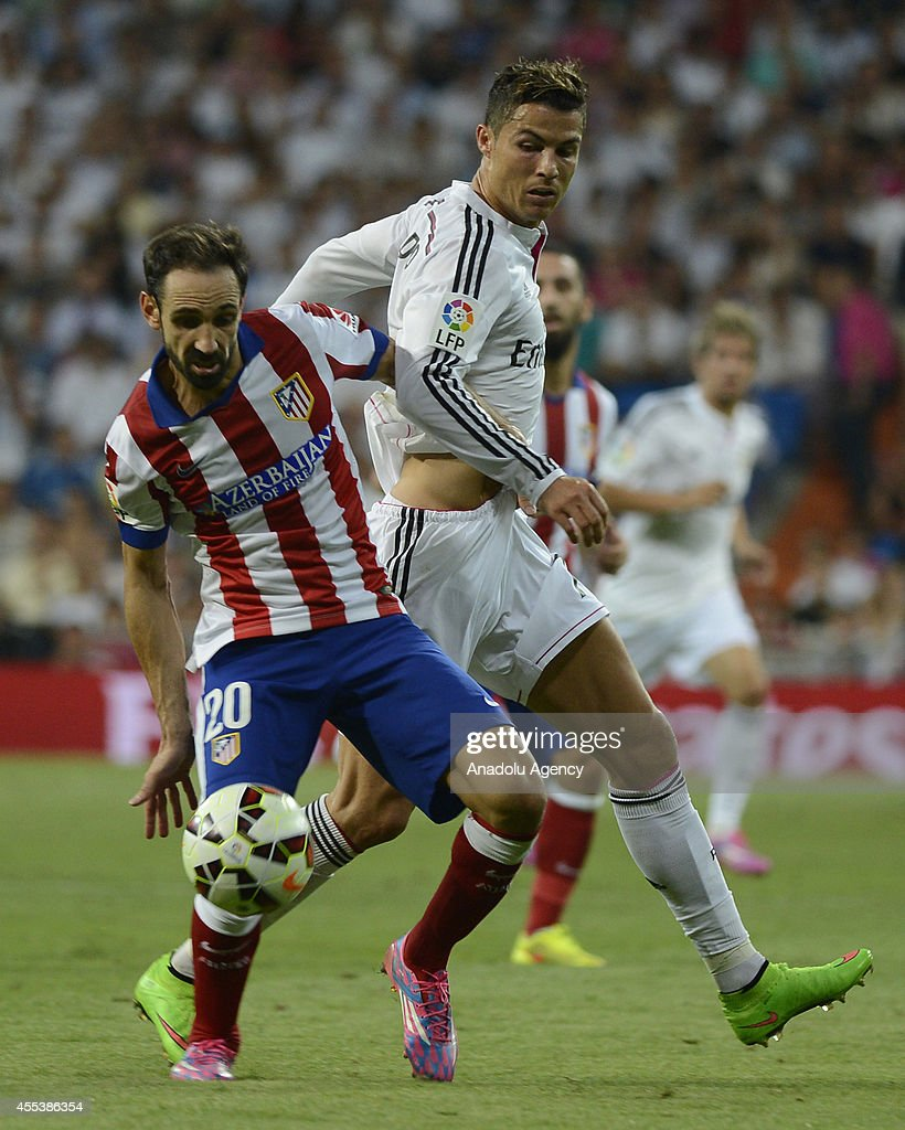 Cristiano Ronaldo (R) of Real Madrid vies for the ball with Juanfran (20) of Atletico Madrid during the Spanish La Liga soccer match between Real Madrid and Atletico Madrid at the Santiago Bernabeu stadium in Madrid, Spain on September 13, 2014.