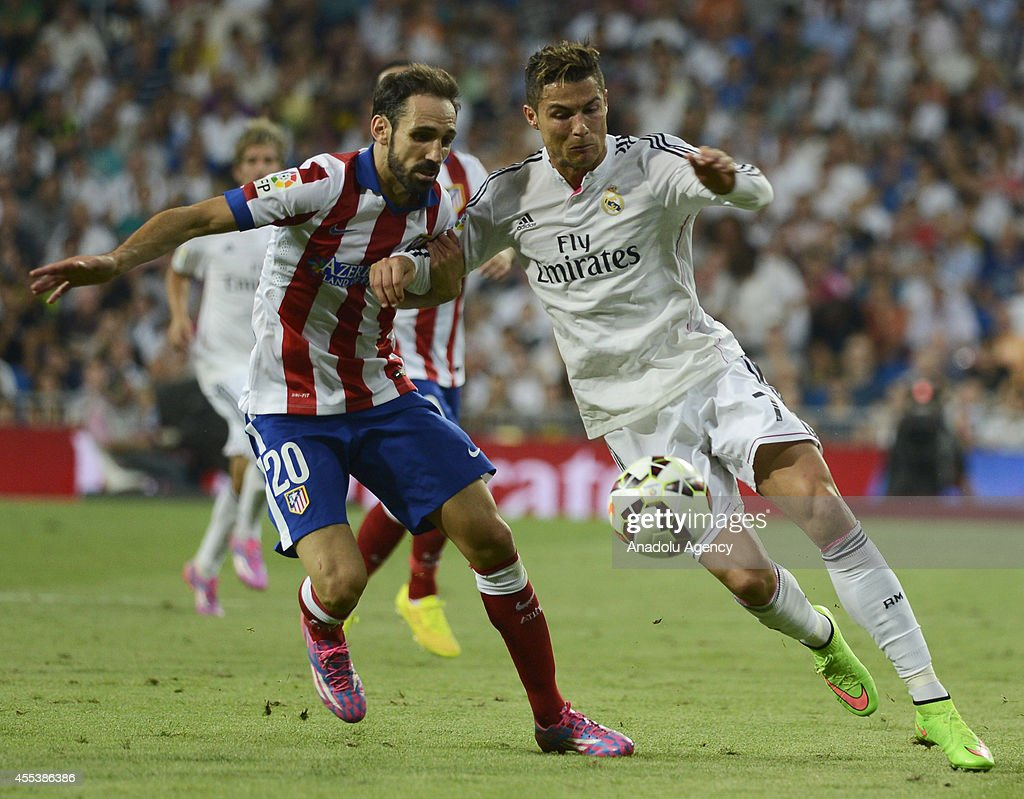 Cristiano Ronaldo (7) of Real Madrid vies for the ball with Juanfran (20) of Atletico Madrid during the Spanish La Liga soccer match between Real Madrid and Atletico Madrid at the Santiago Bernabeu stadium in Madrid, Spain on September 13, 2014.