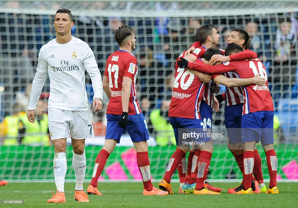 Cristiano Ronaldo of Real Madrid walks away from celebrating Atletico Madrid players after Atletico beat Real 1-0 in the La Liga match between Real Madrid CF and Club Atletico de Madrid at Estadio Santiago Bernabeu on February 27, 2016 in Madrid, Spain.