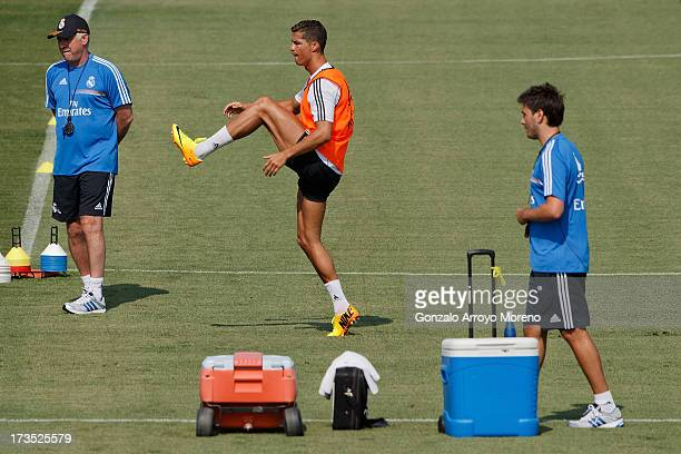 Cristiano Ronaldo of Real Madrid warms up while head coach Carlo Ancelotti looks on and his son Davide Ancelotti walks on during a training session...