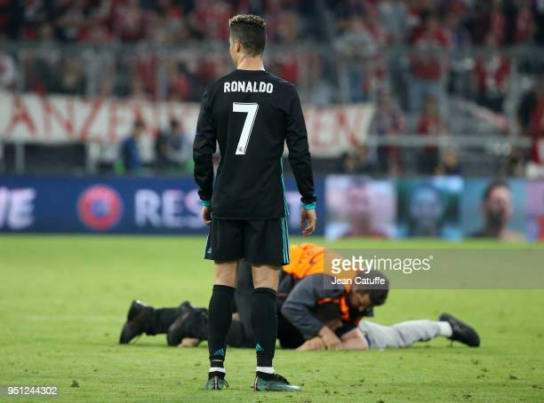 Cristiano Ronaldo of Real Madrid watches a fan who wanted a selfie with him being tackled following the UEFA Champions League Semi Final first leg...