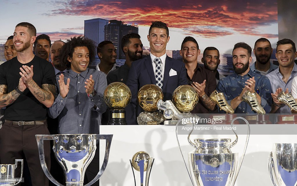 Cristiano Ronaldo poses for a picture with his trophy as all-time top scorer of Real Madrid CF lines up with all his teammates with all trophys at Honour box-seat of Santiago Bernabeu Stadium on October 2, 2015 in Madrid, Spain. Portuguese player Cristiano Ronaldo overtook Raul's goal scoring record on his last UEFA Champions League match against Malmo FF to become Real Madrid's all-time top scorer.