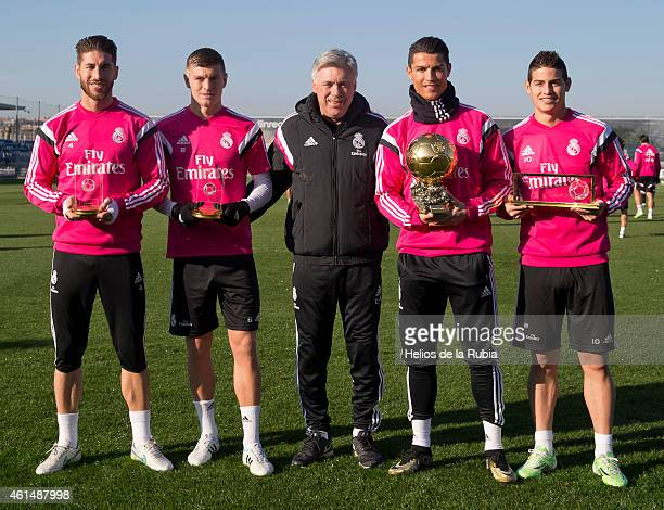 Cristiano Ronaldo poses with his teammates Sergio Ramos Toni Kroos head coach Carlo Ancelotti and James Rodriguez with his Ballon d'Or trophy at...