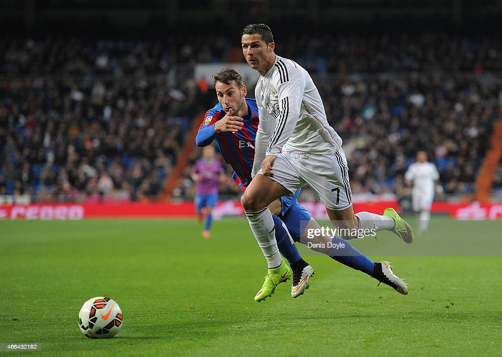 Cristiano Ronaldo runs past Ivan Lopez of Levante during the La Liga match between Real Madrid CF and Levante UD at Estadio Santiago Bernabeu on March 15, 2015 in Madrid, Spain.