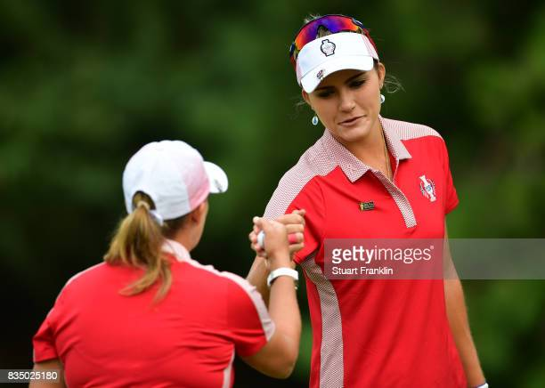 Cristie Kerr and Lexi Thompson of Team USA bump fists during the morning foursomes matches of The Solheim Cup at Des Moines Golf and Country Club on...