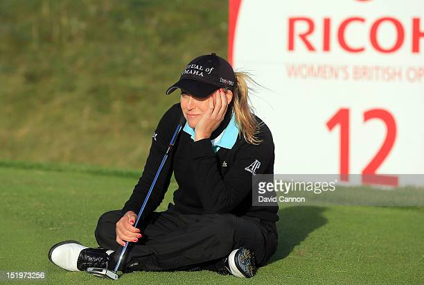 Cristie Kerr of the United States in a more lighthearted moment as she sits and waits on the 12th green for play to be suspended as the course was...