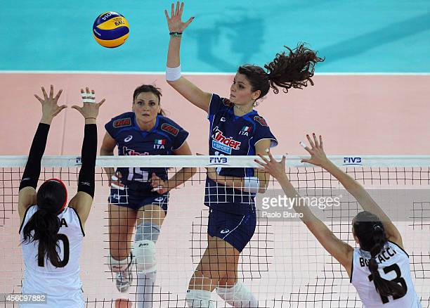 Cristina Chirichella of Italy spikes the ball as Reyes Busquets and Leticia Boscacci of Argentina block during the FIVB Women's World Championship...