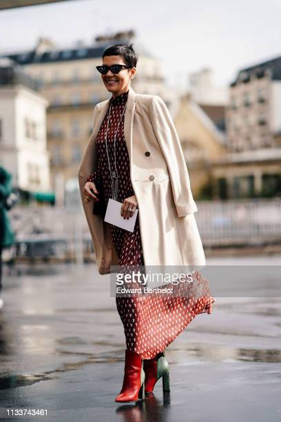 Cristina Cordula wears sunglasses, a white coat, a necklace, a red dress with white dots, red and green ankle boots, outside Giambattista Valli,...
