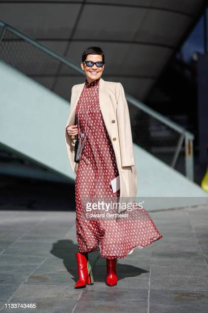 Cristina Cordula wears sunglasses, a white coat, a necklace,a red dress with white dots, red and green ankle boots, outside Giambattista Valli,...