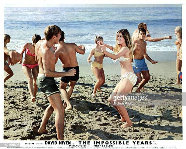 Cristina Ferrare along with other young adults dance in the sand in their bathing suits in a scene from the film 'The Impossible Years' 1968