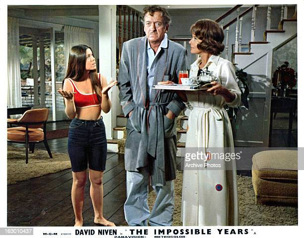 Cristina Ferrare consults with David Niven and Lola Albright in a scene from the film 'The Impossible Years' 1968