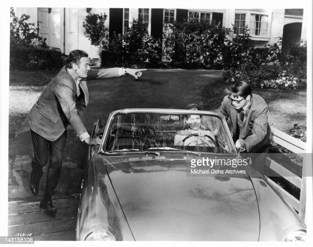 Cristina Ferrare sitting in the drivers seat of a car and David Niven is standing on one side of the car and Chad Everett on the other side talking...