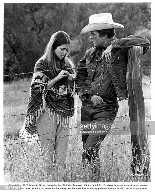 Cristina Ferrare stands by a fence with Cliff Robertson in a scene from the film 'JW Coop' 1971