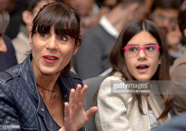 Cristina Guardiola wife of Bayern Munich's German new head coach Pep Guardiola sits next to their daughter Maria during the press conference to...