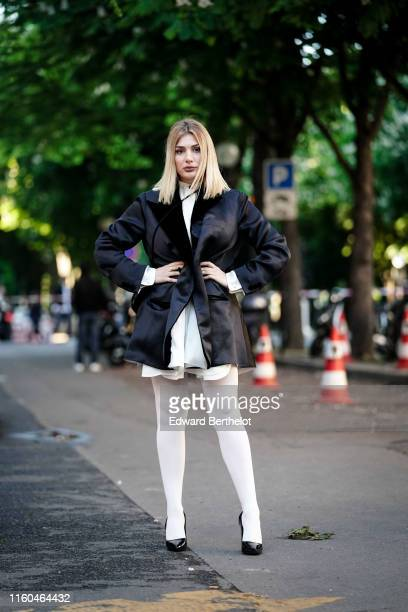 Cristina Musacchio wears a black lustrous oversize satin jacket with velvet lapels white tights black shiny patent leather pointy heeled pumps...