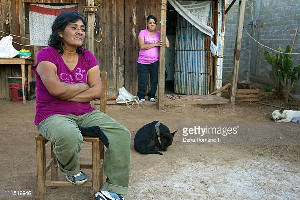 Cristina sits with her daughter Ana outside of their tworoom home on November 15 2009 in the town of San Pablo Huixtepec Christina is a singlemom and...