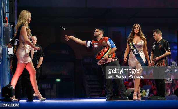 Cristo Reyes plays his practice throws as the William Hill oche girls walk off stage during day eight of the William Hill World Darts Championship at...