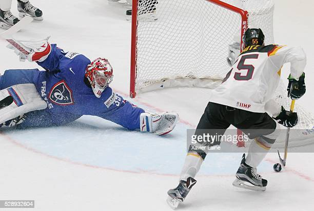 Cristobal Huet of France stop the puck over Felix Schutz of Germany during the 2016 IIHF World Championship between France and Germany at Yubileyny...