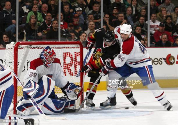 Cristobal Huet of the Montreal Canadiens makes a save in close while teammate Sheldon Souray tries to stop Antoine Vermette of the Ottawa Senators...