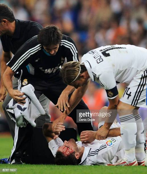 Cristoph Metzelder of Real Madrid is helped by Guti after cutting his head during the La Liga match between Real Madrid and Numancia at the Santiago...