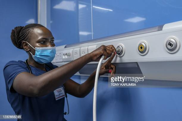 Critical care nurse, Emily Chepng'eno plugs a ventilator machine hose into the Oxygen delivery port during a simulation to demonstrate delivery of...