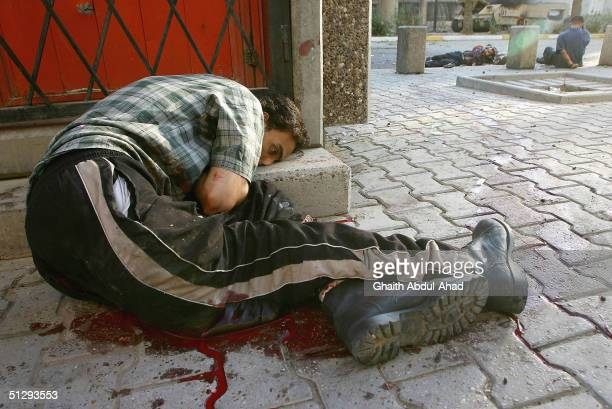 A critically Injured Iraqi civilian takes cover as his life ebbs away on September 12 2004 in Haifa Street Baghdad Iraq Fighting broke out in the...