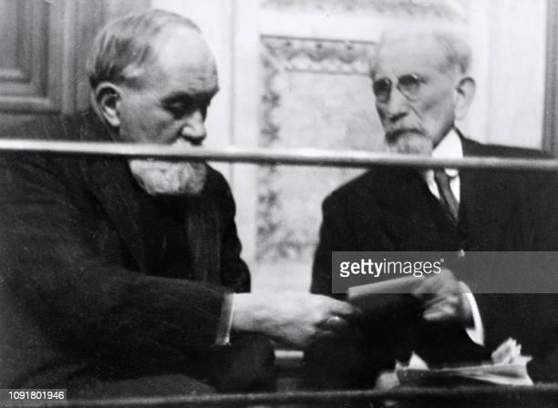 L'écrivain et homme politique Charles Maurras assis sur le banc des accusés donne un papier à l'écrivain Maurice Pujo au cours de leur procès le 25...