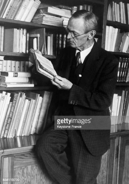 L'écrivain Hermann Hesse qui vient d'être nommé Prix Nobel de littérature photographié dans son bureau lisant un livre en Suisse en 1946