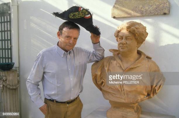 L'écrivain Jacques Laurent pose à côté du buste d'Alexandre Dumas en juillet 1986 en France