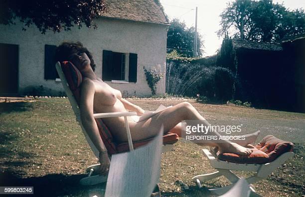 L'écrivain Régine Deforges allongée nue sur une chaise longue en France circa 1960