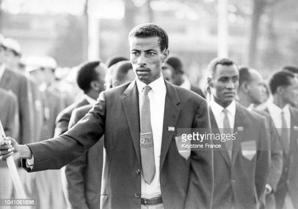 Cérémonie du lever du drapeau éthiopien tenu par le coureur éthiopien Abebe Bikila au village olympique en octobre 1964 à Tokyo Japon