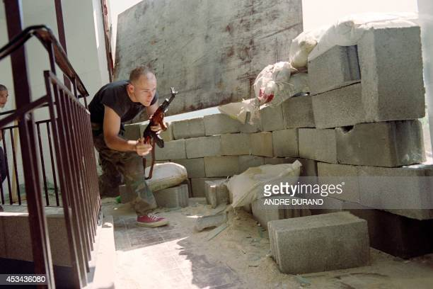 A Croat militiaman runs in a crouch on July 30 1992 as he takes up a position a couple of hundred meters from Serb forces in the Bosnia capital...