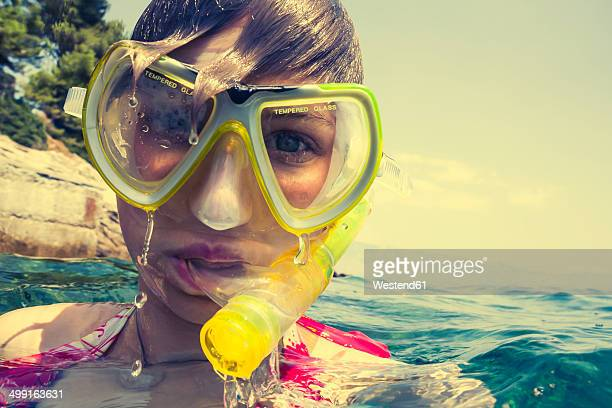 Croatia, Brac, Sumartin, Teenage girl in water with diving goggles and snorkel