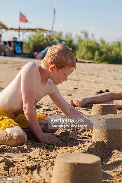 Croatia, Dalmatia, Boy On Beach Building Sandcastle